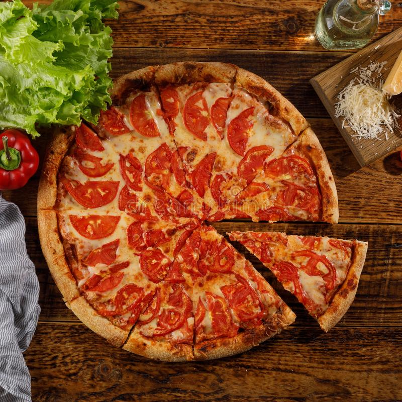 Pizza Margarita on a wooden table. Still life. Look at the top. Square royalty free stock images