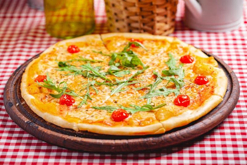 Pizza Margherita Margarita med ny arugula på träbräde royaltyfri fotografi