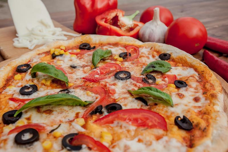 Pizza Margherita or Margarita with Mozzarella cheese, tomato, olive. Italian pizza on wooden background stock photography