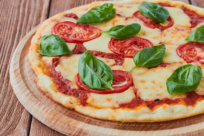 Pizza Margherita med tomater, mozzarellaen och basilika arkivfoton
