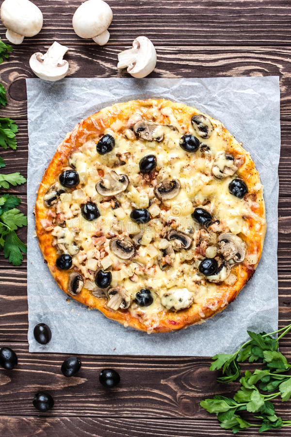 Pizza with meat, mushrooms, pineapple and olives on a wooden bac. Delicious with meat, mushrooms, pineapple and olives on a wooden background stock photos