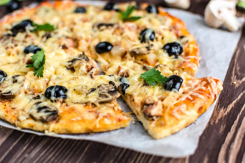 Pizza with meat, mushrooms, pineapple and olives on a wooden background. Delicious with meat, mushrooms, pineapple and olives on a wooden background stock images