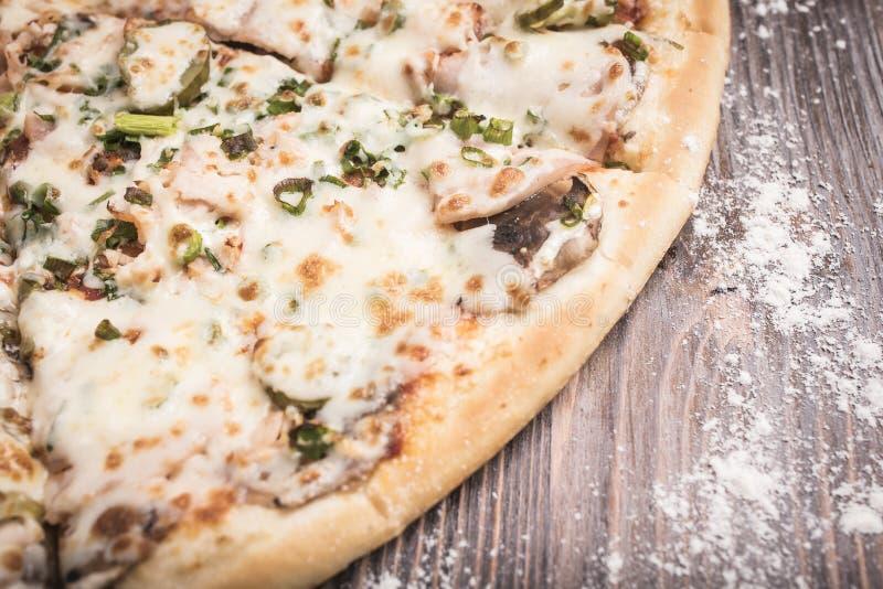Pizza med champinjoner och inlagd gurkanärbild på en brun träbakgrund arkivbild
