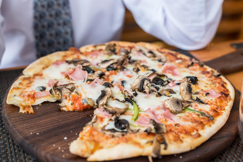 Pizza med champinjoner på tabellen i restaurang arkivfoto