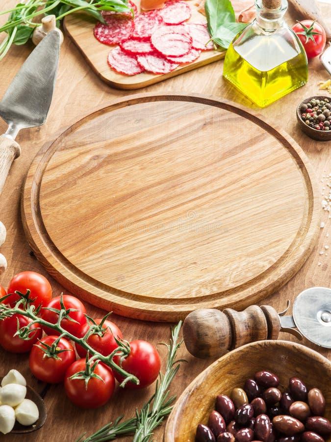 Pizza med champinjoner, salami och tomater arkivbild