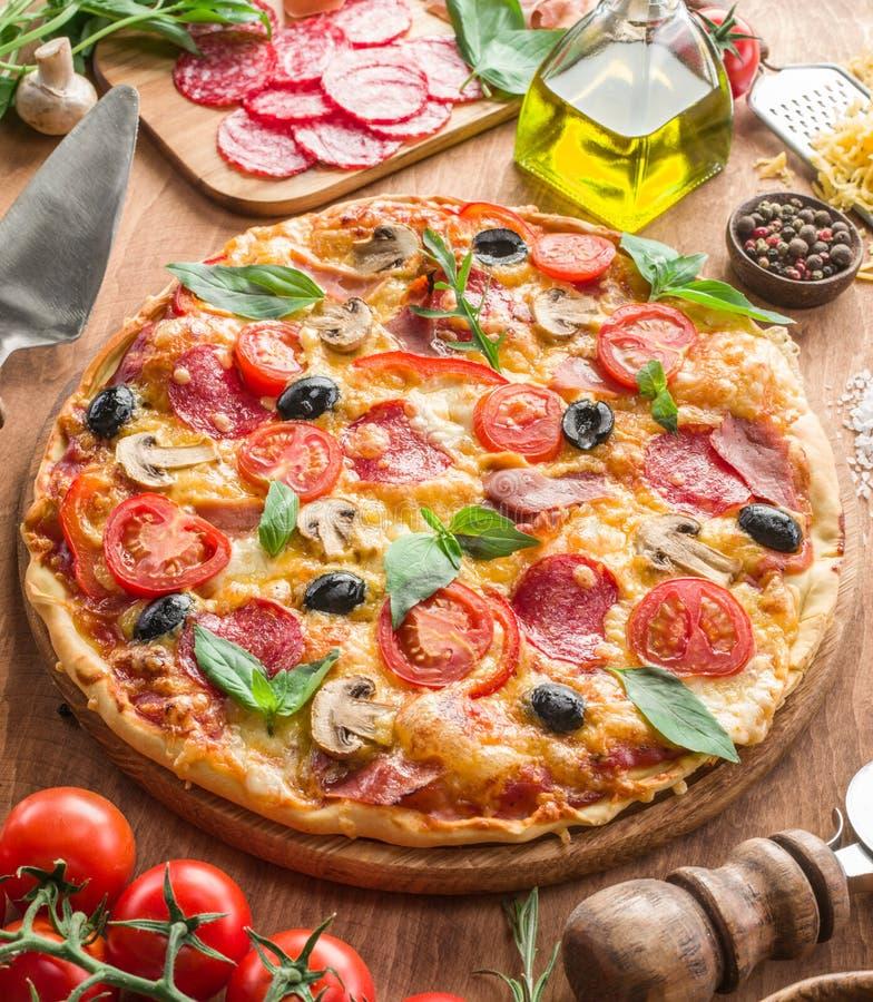Pizza med champinjoner, salami och tomater arkivbilder