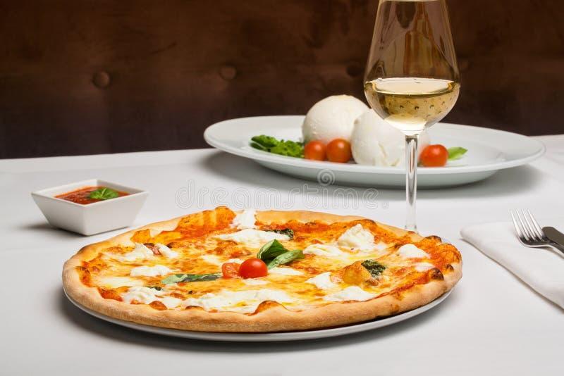 Pizza med laxen och mozzarellaen på bakgrunden i en lokal shoppar pizzeria med ett exponeringsglas av vitt vin royaltyfri foto