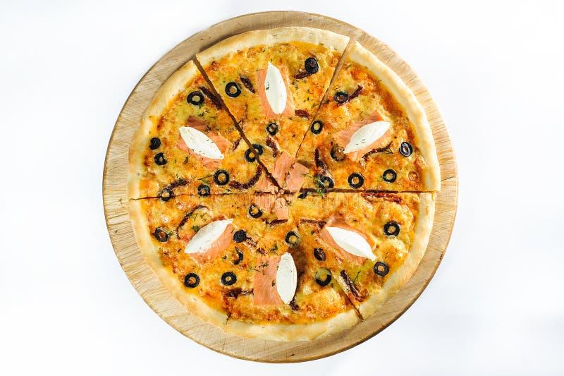 Pizza med laxen på träbakgrund royaltyfri bild