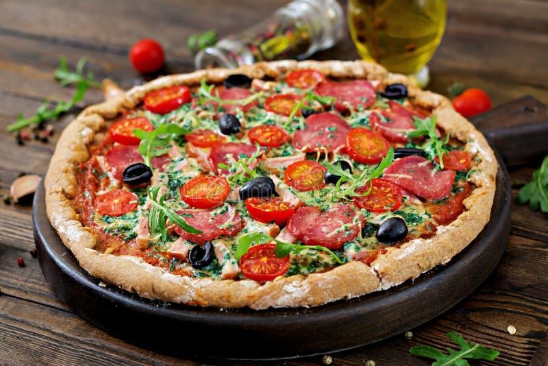 Pizza med salami, tomater, oliv och ost på en deg royaltyfri foto