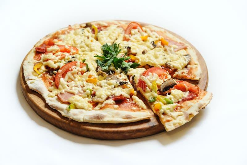 Pizza med skinka, champinjoner och tomater royaltyfria foton