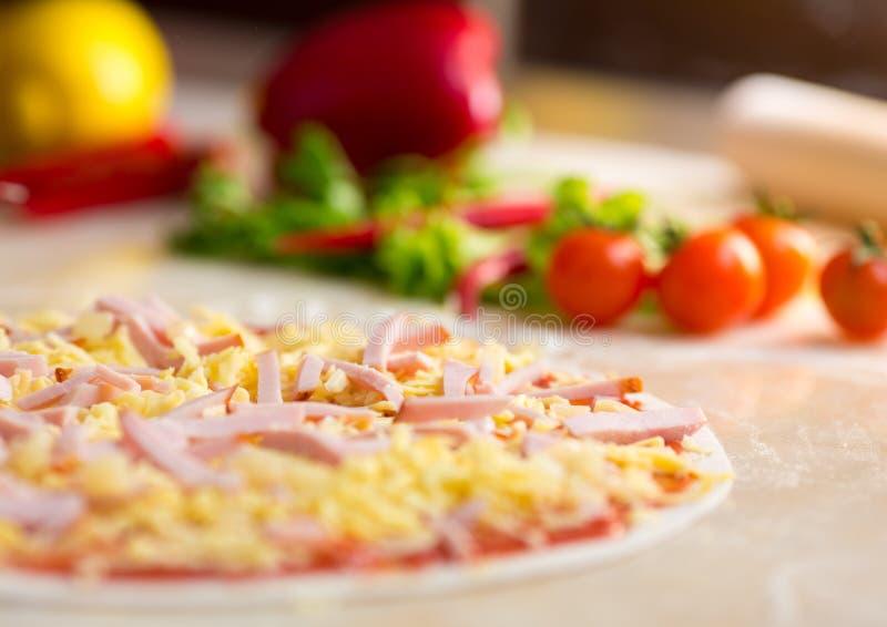 Pizza med skinkaförberedelsen royaltyfri foto
