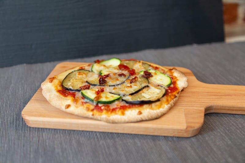 Pizza med zucchinin, aubergine och torra tomater med gratängmozzarellaost royaltyfri foto