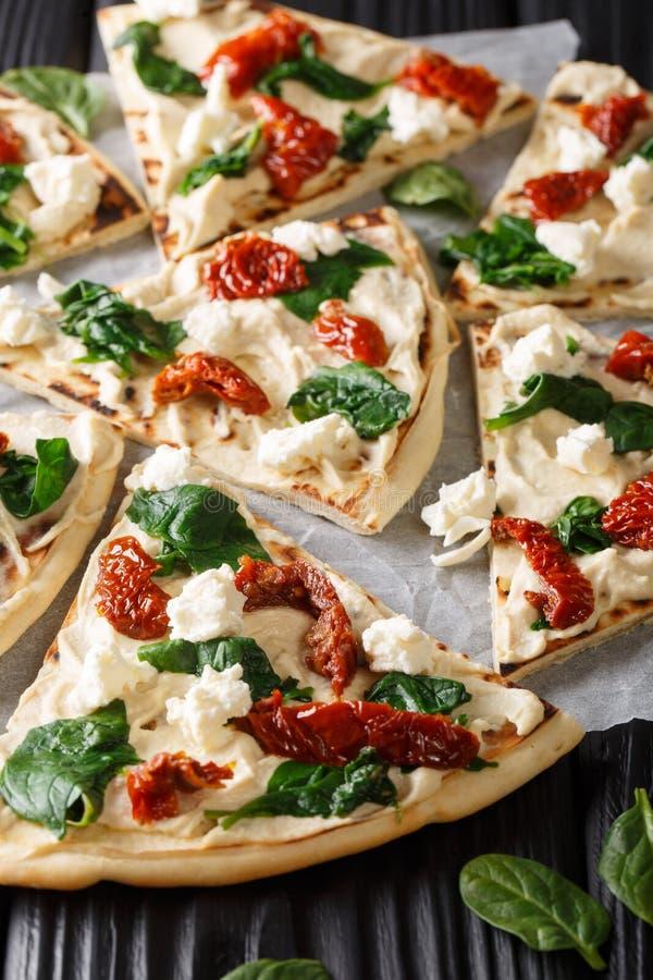 Pizza medio-oriental con hummus, el primer secado al sol del queso de los tomates, de la espinaca y de cabra vertical fotos de archivo libres de regalías