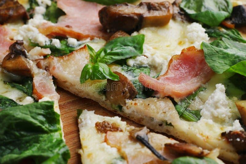 Pizza met afgesneden baconpaddestoelen en basilicum dicht omhooggaand één stuk stock afbeeldingen