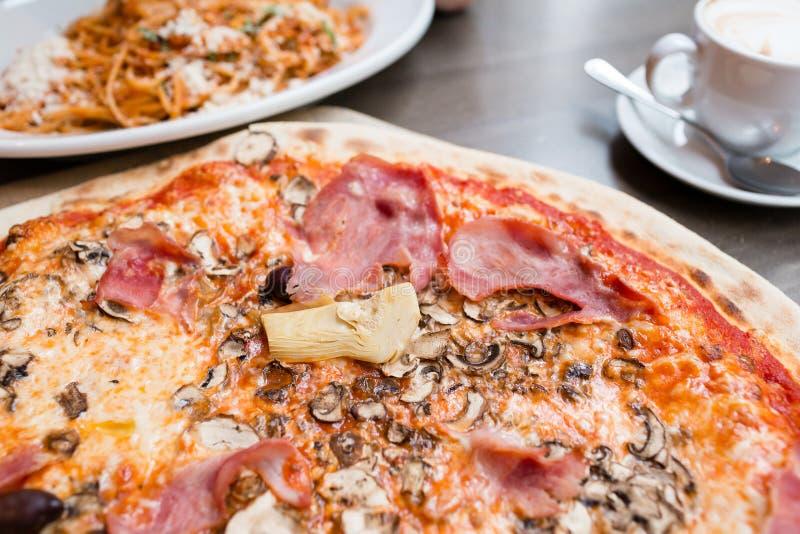 Pizza met artisjok, ham en paddestoelen het proces om te eten, kooktoestellen royalty-vrije stock foto