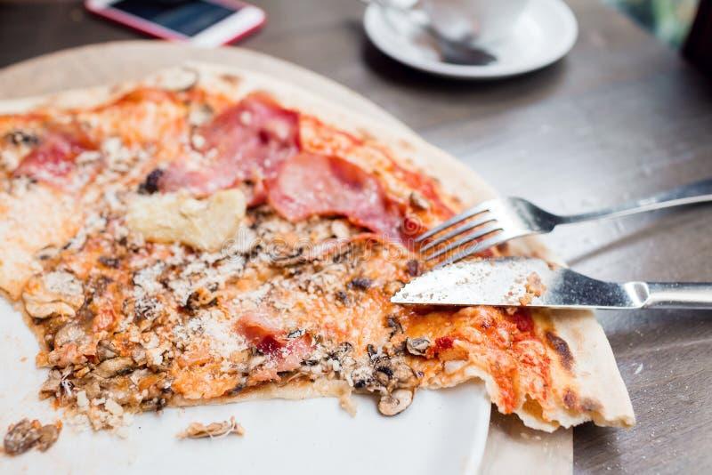 Pizza met artisjok, ham en paddestoelen het proces om te eten, kooktoestellen royalty-vrije stock afbeelding