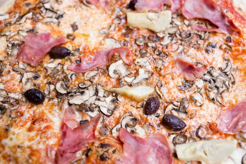 Pizza met artisjok, ham en paddestoelen het proces om te eten, kooktoestellen royalty-vrije stock fotografie