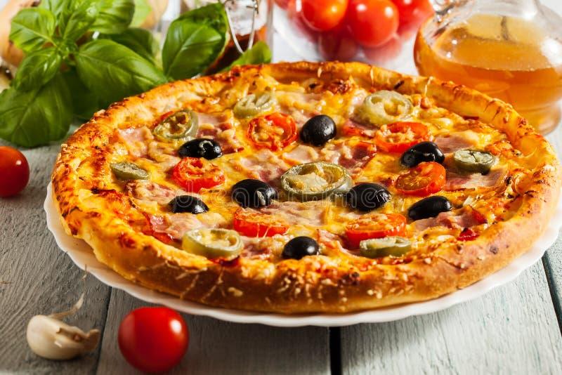 Pizza met bacon, olijven en jalapenopeper stock afbeeldingen