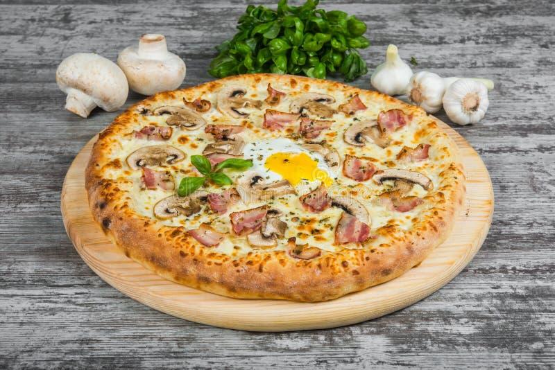 Pizza met bacon, paddestoelen en ei, met rozemarijn en kruiden stock afbeelding