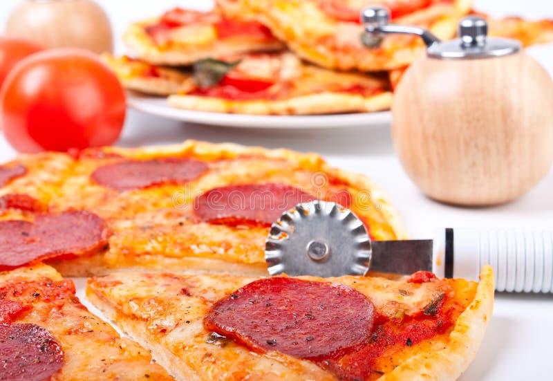 Pizza met een pizza-mes stock afbeeldingen