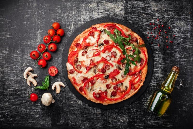 Pizza met gerookte worsten, kaas, paddestoelen, kersentomaten, groene paprika's en greens op een steen stock afbeeldingen