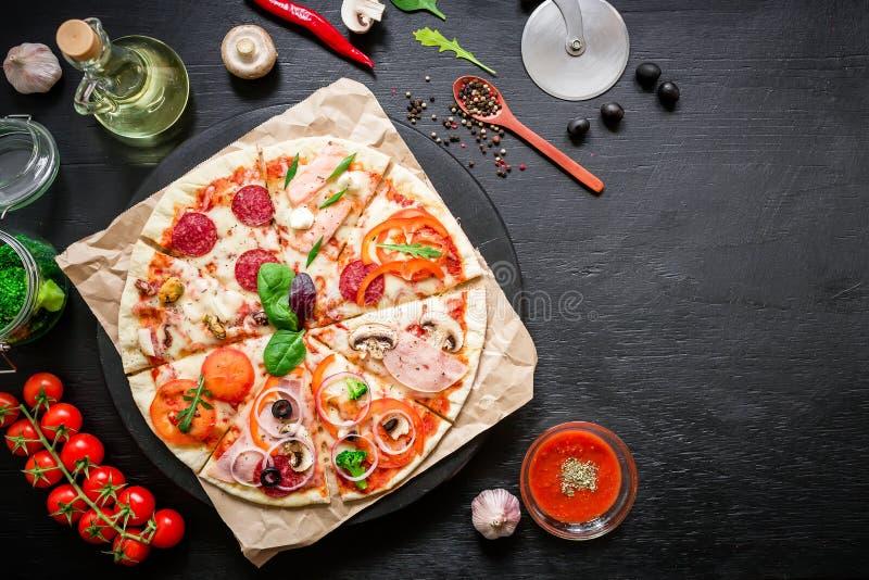 Pizza met ingrediënten, kruiden, olie en groenten op donkere lijst Vlak leg, hoogste mening stock foto's