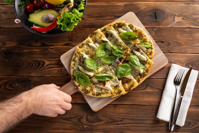 Pizza met kip, paddestoelen en kaas en de hand van de man die de raad houdt royalty-vrije stock afbeeldingen