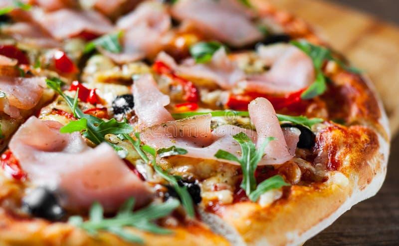 Pizza met Mozarellakaas, ham, peper, olijf, vlees, Tomatensaus, Kruiden en Verse arugula stock foto