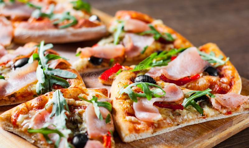 Pizza met Mozarellakaas, ham, peper, olijf, vlees, Tomatensaus, Kruiden en Verse arugula stock foto's