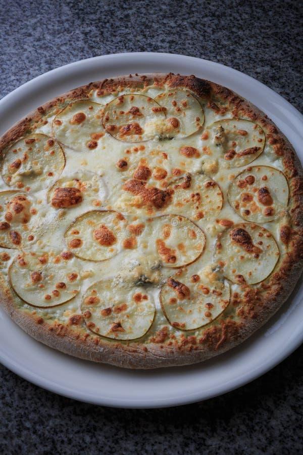 pizza met peer en gargantilla op een witte plaat stock afbeelding