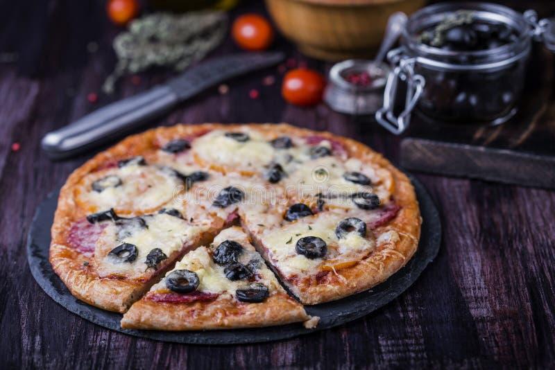 Pizza met salami, mozarella, olijven en basilicum stock foto
