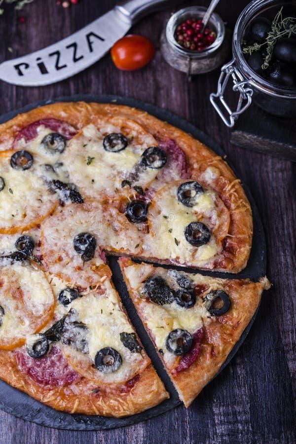 Pizza met salami, mozarella, olijven en basilicum royalty-vrije stock afbeelding