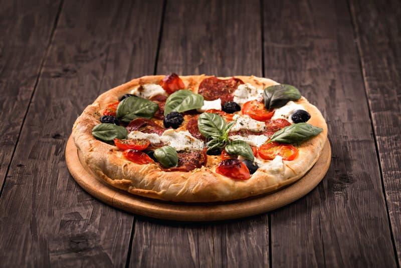 Pizza met salami, mozarella, olijven en basilicum op houten lijst stock foto's