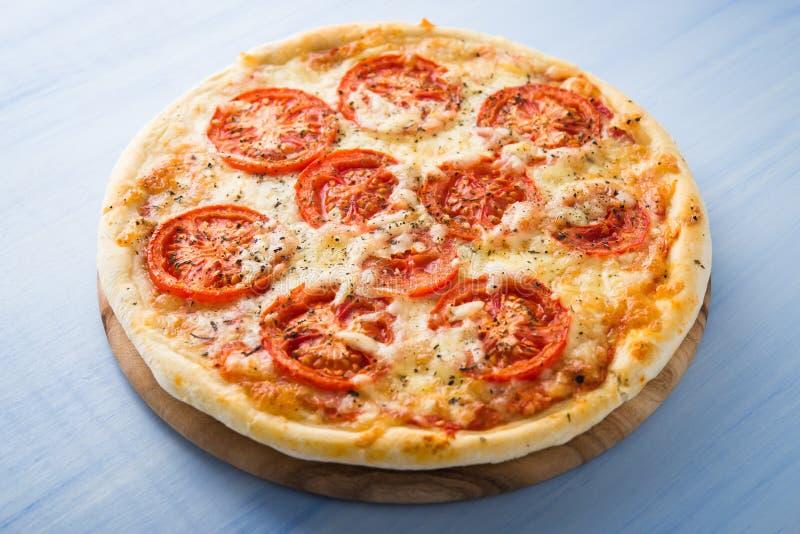 Pizza met tomaat, kaas en droog basilicum op blauwe houten dichte omhooggaand als achtergrond royalty-vrije stock fotografie