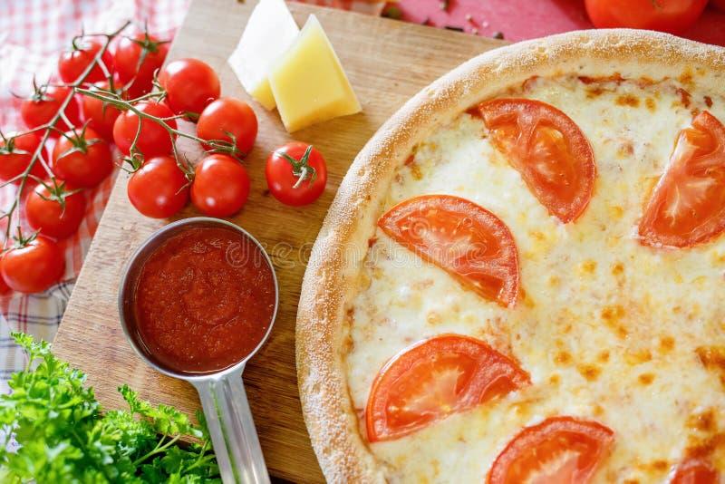 Pizza met tomaat op een houten raad stock foto