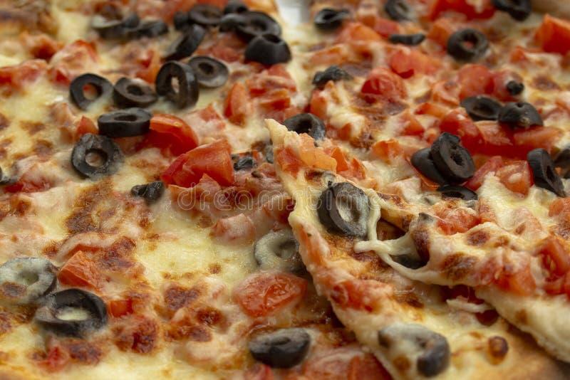 Pizza met vers tomaten, olijven, mozarella, olijfolie en basilicum close-up royalty-vrije stock foto's