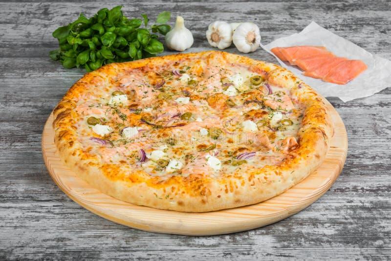 Pizza met zalm rode vissen, met rozemarijn en kruiden op een lichte houten achtergrond stock fotografie