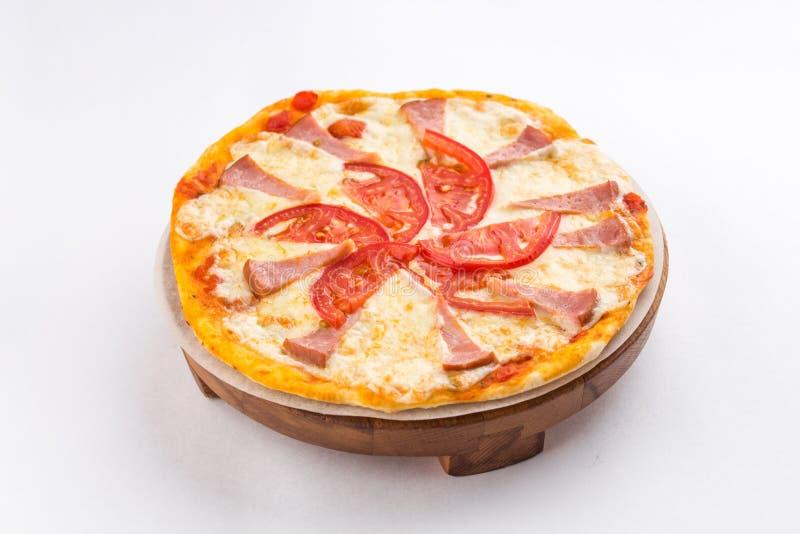 Pizza mit den Tomaten und Schinken lokalisiert auf wei?em Hintergrund lizenzfreie stockfotos