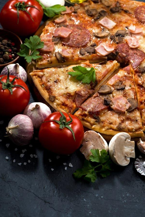 Pizza mit der Wurst und Käse und Bestandteile, vertikal stockfotografie