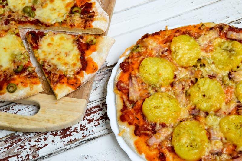 Pizza mit Kartoffeln und Speck und Pizza mit Käse stockbild