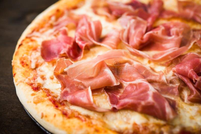 Pizza mit Prosciutto u. x28; Parma-ham& x29; auf dunklem hölzernem Hintergrundabschluß oben lizenzfreies stockbild