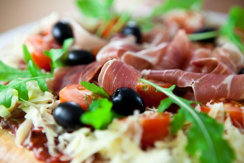 Pizza mit prosciutto und Oliven lizenzfreies stockfoto
