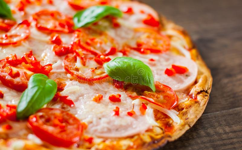 Pizza with Mozzarella cheese, Ham, Tomatoes, pepper, Spices and Fresh Basil. Italian pizza on wooden royalty free stock images