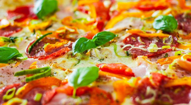 Pizza with Mozzarella cheese, Ham, Tomatoes, salami, pepper, pepperoni Spices and Fresh Basil. Italian pizza royalty free stock photos
