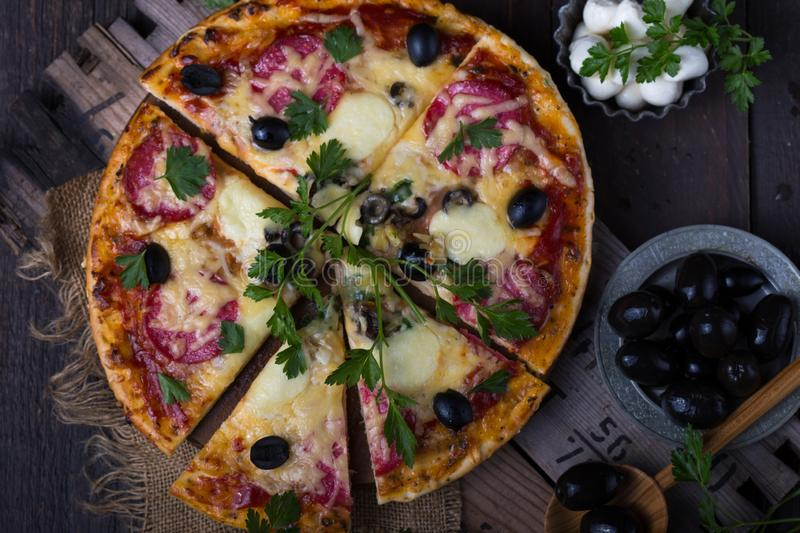 Pizza with mozzarella, mushrooms, black olives and fresh basil. Italian pizza. Homemade food. Symbolic image. Concept for a tasty. And hearty meal. Rustic royalty free stock photography