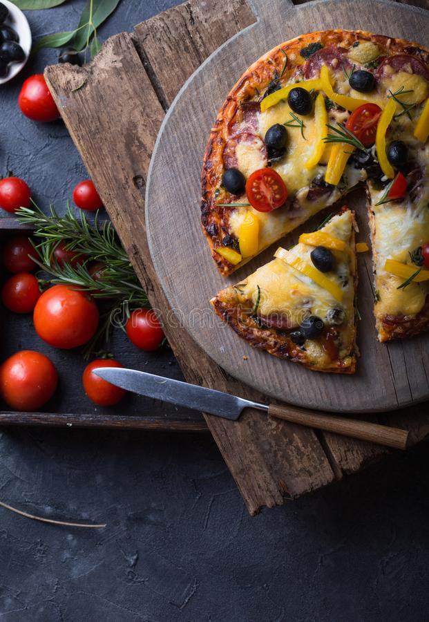 Pizza with mozzarella, mushrooms, black olives and fresh basil. Italian pizza. Homemade food. Symbolic image. Concept for a tasty. And hearty meal. Rustic stock photo