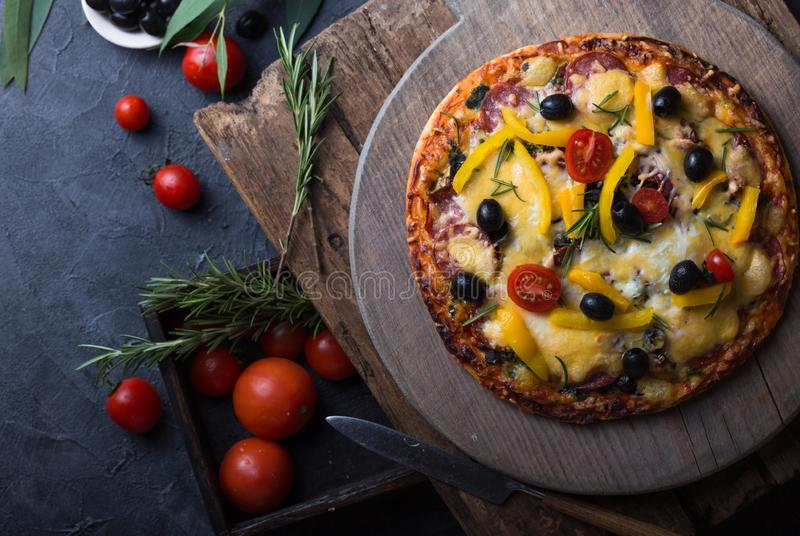 Pizza with mozzarella, mushrooms, black olives and fresh basil. Italian pizza. Homemade food. Symbolic image. Concept for a tasty. And hearty meal. Rustic royalty free stock image