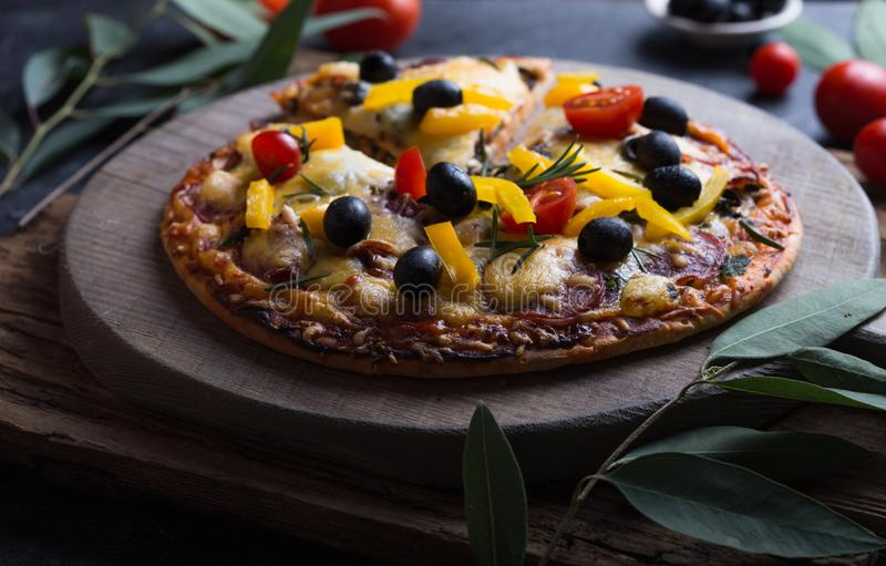 Pizza with mozzarella, mushrooms, black olives and fresh basil. Italian pizza. Homemade food. Symbolic image. Concept for a tasty. And hearty meal. Rustic royalty free stock photo
