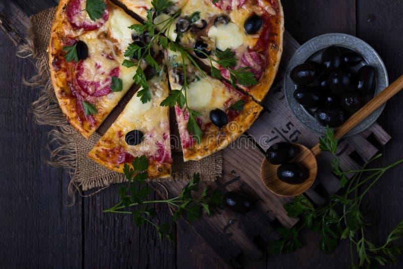 Pizza with mozzarella, mushrooms, black olives and fresh basil. Italian pizza. Homemade food. Symbolic image. Concept for a tasty. Pizza with mozzarella stock image
