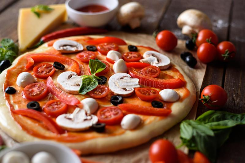 Pizza with mozzarella, olives, mushrooms, cherry tomatoes, bell peppers and herbs before baking stock photography
